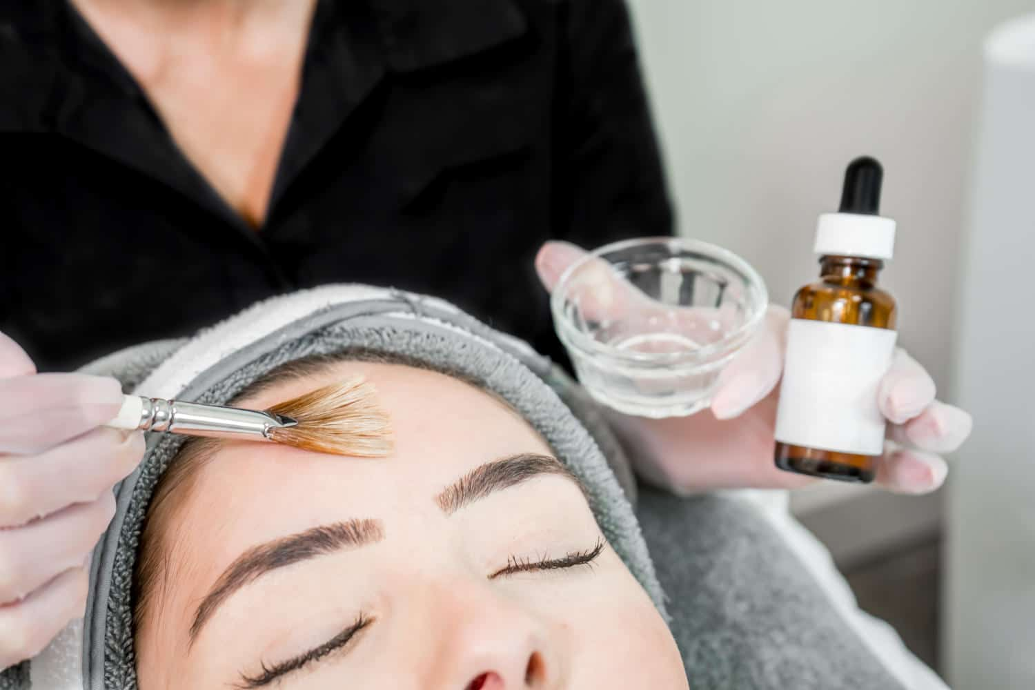 Close up of beautician (cosmetologist) applying chemical peel tr